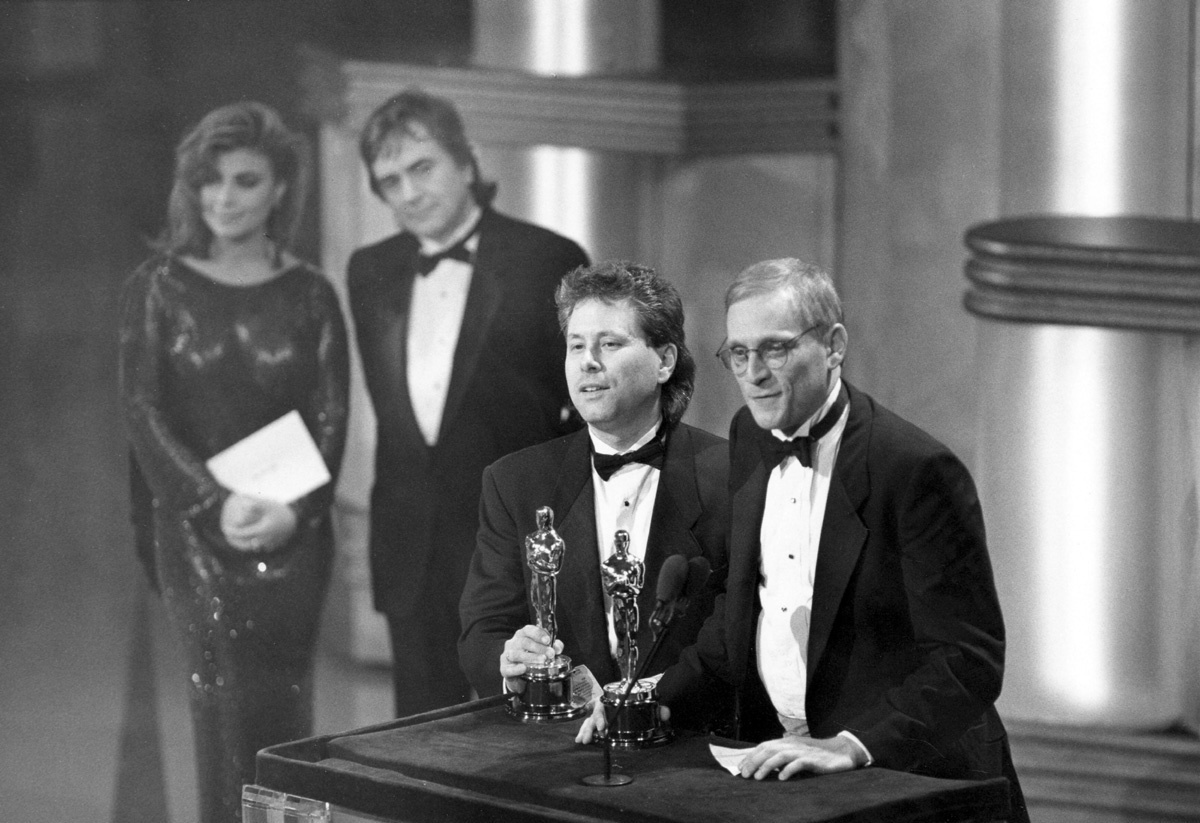 "Alan Menken (music) and Howard Ashman (lyrics) accept their Oscars for Best Original Song for ""Under the Sea,"" from the film THE LITTLE MERMAID (1989). Behind them are presenters Paula Abdul and Dudley Moore. Credit: Long Photography / ©A.M.P.A.S."